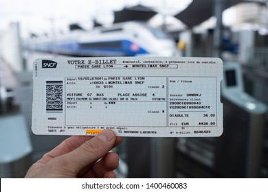 Paris, France, 16 May 2019. Train ticket at Gare de Lyon railway station. Ticket close up against blurry train.