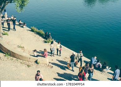 Paris, France, 17 May 2020:  people walk along the embankment, City residents wear masks when walking in Paris. Picnic on the river.