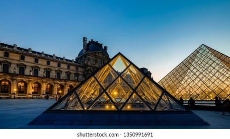Paris, France - 18 Apr 2018: Aerial view of the most famous triangle architecture in the world. Louvre Museum (Musee du louvre) with Beautiful Sunset Clear Sky at Blue Hour.