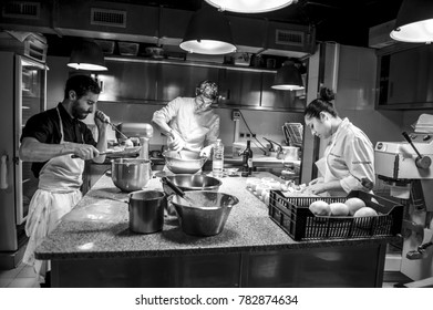 PARIS, FRANCE - 18TH JULY 2016: Three chefs are preparing pastries in the kitchen of a fancy restaurant in Paris.