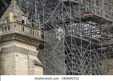 PARIS, FRANCE - 19 APRIL 2019 Notre Dame cathedral, a man positions sandbags along the edge of the walls. The remains of the melted scaffolding behind him is witness to the heat generated by the fire