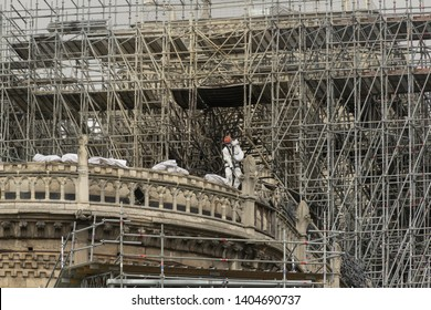 PARIS, FRANCE - 19 APRIL 2019 Notre Dame cathedral, a man removes charred timber from the roof. The remains of the melted scaffolding behind him is witness to the heat generated by the fire