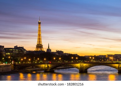 PARIS, FRANCE - 19TH MARCH 2014: The Eiffel Tower at Night with the River Seine in the foreground