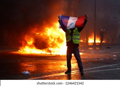 Paris, France.  1st December 2018. . Demonstrators light a car  on fire during a protest of the yellow jackets.