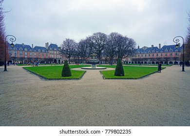 PARIS, FRANCE -20 DEC 2017- View of the Place des Vosges (Place Royale), a Renaissance square with pink buildings in the Marais neighborhood of Paris, France.