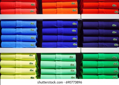 PARIS, FRANCE -20 JUL 2017- Piles of colorful Lacoste polo shirts on store shelves. Lacoste is a French clothing company famous for its tennis shirts.