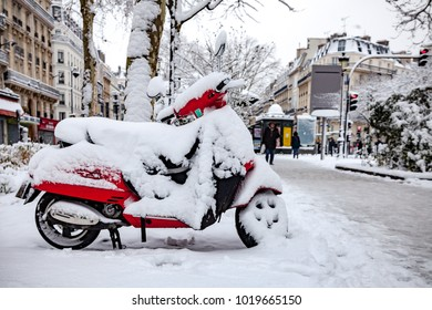 Paris, France - 2018, February 7th: Red scooter covered by snow.
