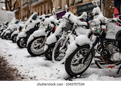 Paris, France - 2018, February 7th: Stationary snow covered motorcycles.