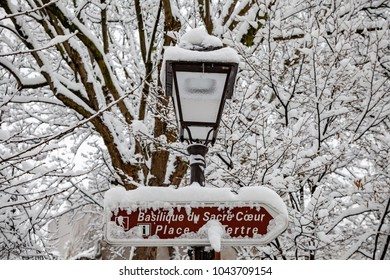 Paris, France - 2018, February 7th: Snow street lamp and sign indicating Sacré-Cœur and Place du Tertre direction in Montmartre.
