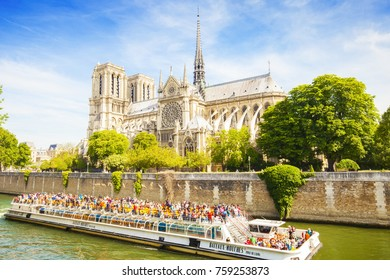 PARIS, FRANCE - 21 May 2017: Notre-Dame Cathedral catholic church building and Seine river boat cruise, many tourists making photos