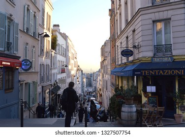 PARIS, FRANCE - 22 FEBRUARY 2019:Early evening on one of the steep cobbled streets of Montmartre, Rue Tholoze at its intersection with Rue Lepic.