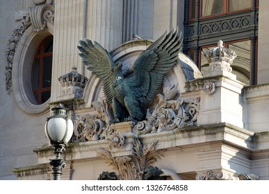 PARIS, FRANCE - 23 FEBRUARY 2019: An eagle sculpture by Pierre Loiuis Rouillard (1820-1881), and pigeon, look out from the western facader of Garnier's Paris Opera