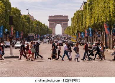 Paris, France - 23 June 2018: A crowd of people crossing Avenue des Champs-Elysees with Arc de Triomphe in the Background