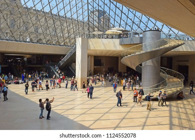PARIS, FRANCE -23 may 2018 :  tourists in the central hall, inside the Louvres pyramid before the inspection of the museum exposition. The museum was inaugurated in 1739