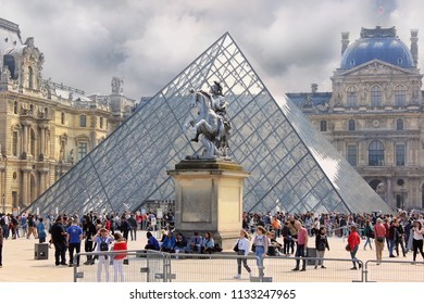 PARIS, FRANCE -23 may 2018 :  tourists before Glass Pyramid, main entrance to the Louvre Museum and statue of Louis XIV - king of France in the foreground. The museum was inaugurated in 1739