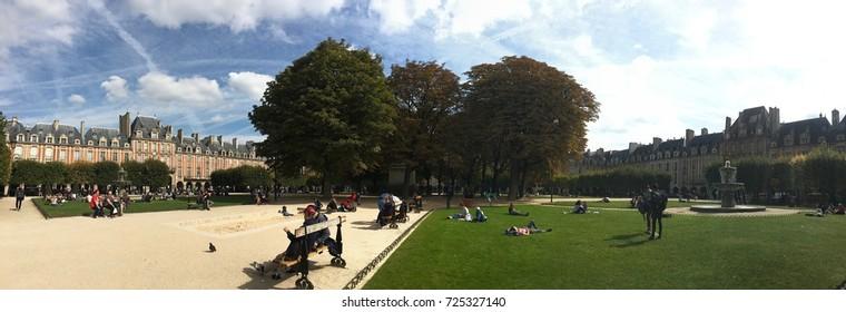 Paris France, 23 September 2017: Tourists seating in the park at Place des Vosges Paris