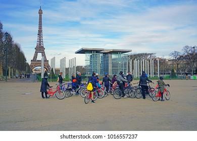 PARIS, FRANCE -24 DEC 2017- Tourists on a biking tour of Paris in front of the iconic Eiffel tower, the most famous landmark in Paris.
