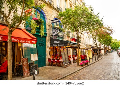 Paris, France - 24.04.2019: Latin Quarter. Narrow street of Paris among old traditional parisian houses and cafe in Paris in France
