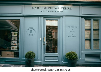 Paris, France, 30.09.2019 Window of the grocery stoore, typical french street with shops on the first floor in house. Vintage shop with vitrine, showcase in blue colors.
