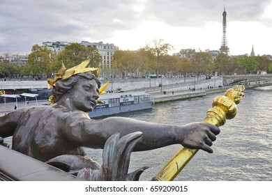 PARIS, FRANCE -7 NOV 2016- Ornate black and gold statues on the Pont Alexandre III bridge over the River Seine in Paris, connecting the Invalides area to the Champs-Elysees neighborhood.