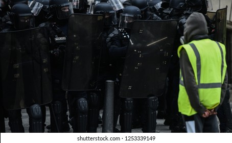 Paris, France - 8 December 2018: Yellow Vests (Gilets jaunes) protester stands in front of French riot police officers during a protests against living costs and rising oil prices