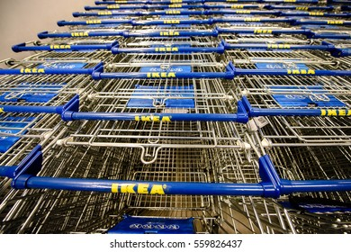 PARIS, FRANCE - APR 12, 2016: Empty supermarket carts in IKEA furniture supermarket store. Point of view of a customre over the supermarket aisle, and ikea logo