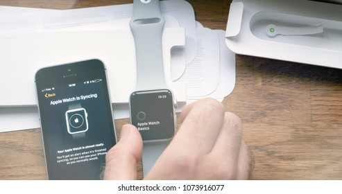 PARIS, FRANCE - APR 12 2018: POV man unboxing unpacking latest Apple Watch Series 3 GPS LTE smartwatch Apple Watch basics on the screen of watch next to iPhone SE