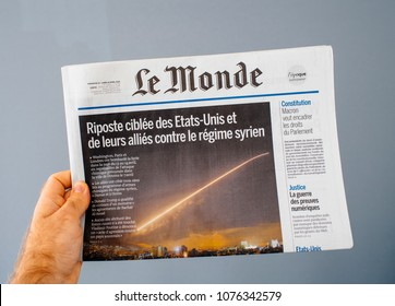 PARIS, FRANCE - APR 15, 2014: Le Monde French newspaper in man hand with cover showing Bombing Syria missle by Washington, London and Paris
