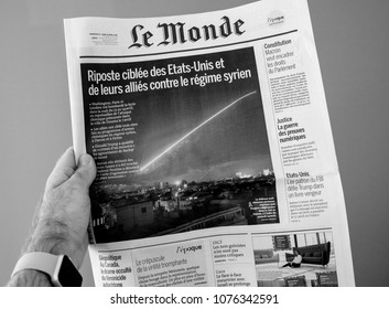 PARIS, FRANCE - APR 15, 2014: Le Monde French newspaper in man hand with cover showing Bombing Syria missle by Washington, London and Paris - black and white