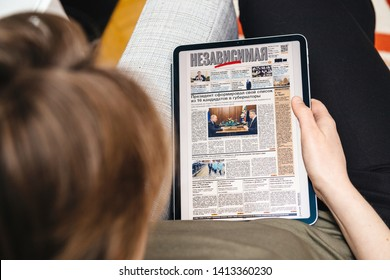 Paris, France - Apr 15, 2019: Woman reading on iPad Pro Apple News Plus Nezavisimaya Gazeta digital newspaper featuring breaking neabout 16 governors list made by Vladimir Putin Russian President