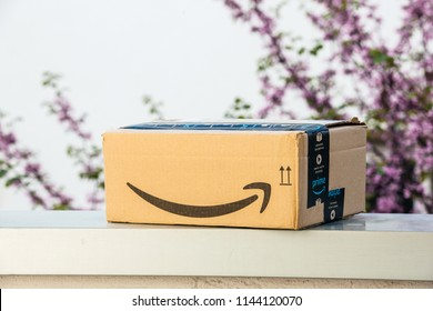 PARIS, FRANCE - APR 19, 2018: Side view of new Amazon Cardboard box left outdoor the house by courier with large Amazon Smile logotype against defocused tree background