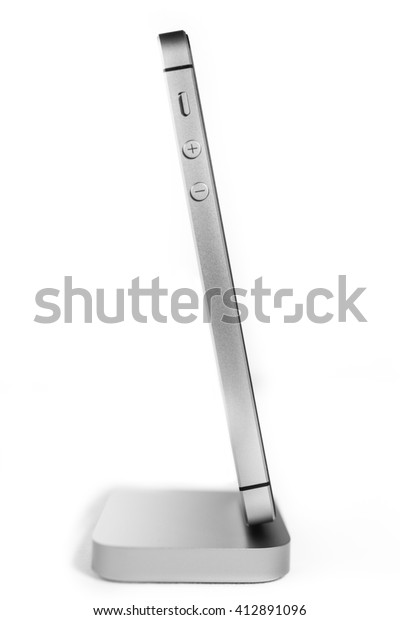 PARIS, FRANCE - APR 21, 2016: Side view of the new Apple iPhone SE in docking station combining the updated processor, 4K rear camera, touch id, retina display