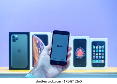 Paris, France - Apr 26, 2020: Man holding iPhone SE with Hallo word with multiple packages cardboards of Apple Computers iPhone smartphpone iPhone 3gs, SE 2016, XS and 11 Pro