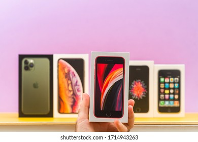 Paris, France - Apr 26, 2020: Man holding Se 2020 phone box with multiple packages cardboards of Apple Computers iphone smartphpone iPhone 3gs, SE 2016, SE 2020, XS and 11 Pro with triple cameras -