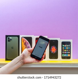 Paris, France - Apr 26, 2020: Woman hand holding latest iPhone SE 2020 red phone with multiple packages cardboards of Apple Computers iPhone smartphpone iPhone 3gs, SE 2016, XS and 11 Pro