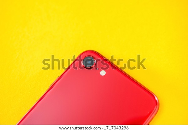Paris, France - Apr 26, 2020: Close-up macro shot of single camera on red new budget iPhone SE by Apple Computers touch ID, Single-lens rear camera and iPhone 8 design with internals from 11 Pro