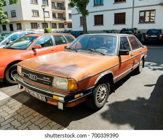 PARIS, FRANCE - APR 28, 2017: Vintage AUDI 100 orange color parked on French street. The Audi 100 and Audi 200 are four-door, front-engine, front- or all-wheel drive full-size/executive sedans