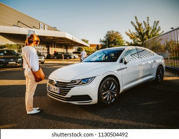 PARIS, FRANCE - APR 8, 2017: Buying new car - new white Volkswagen Passat wagon car admired by woman near the dealership
