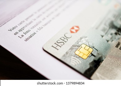 Paris, France - Apr 9, 2017: Tilt-shift lens focus over new HSBC French division featuring Arc de Triumph on the cover Visa Maestro card received in white envelope and instruction how to use it