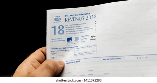 Paris; France - Apr 9; 2019: Man holding declaration des revenus preremplie income pre-filled statement to French authorities and income tax instruction for previous year - direction generale des