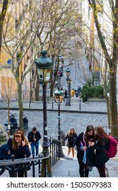 Paris, France - April 08, 2019: People on Montmartre Stairs going up and down next to Funiculaire inclined train station