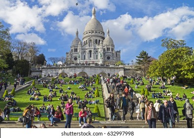 PARIS, FRANCE - APRIL 1, 2017: Tourists on the hillside of Montmartre on the background of the Sacre-Coeur basilica. The beginning of April. Paris, France.