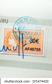 PARIS, FRANCE - APRIL 10, 2014: Revenue stamp or tax stamp or fiscal stamp issued by Republic of France in a value of 30 Euros, marked with a seal and signature as seen on a document on April 10, 2014