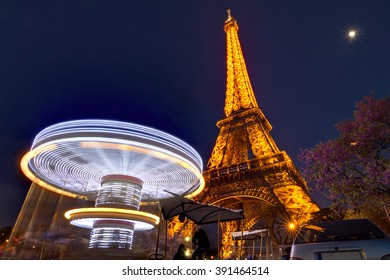 PARIS, FRANCE - APRIL 10, 2014: Beautiful view of the Eiffel tower at night with a carousel in front of it and the moon in the sky in Paris, France, on April 10, 2014
