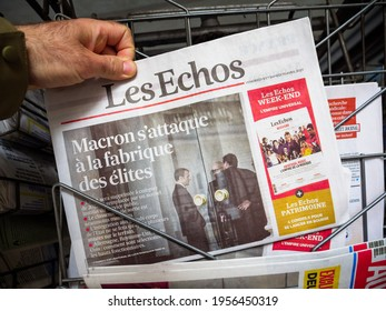 Paris, France - April 11, 2021: POV male hand buying Les Echo French newspaper with breaking news Emmanuel Macron closing ENA Ecole nationale d'administration, the symbol of an elite school