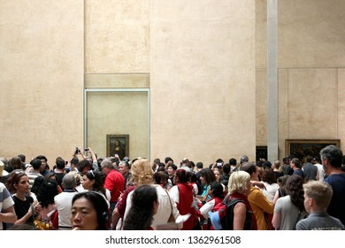 PARIS, FRANCE - APRIL 12, 2018: Tourists take photos of Leonardo DaVinci's Mona Lisa (La Gioconda) at the Louvre Museum, Paris