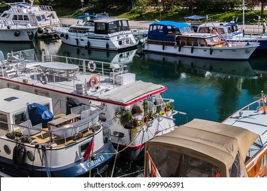 PARIS, FRANCE - APRIL 13, 2017: Row of houseboats docked on Canal Saint Martin in Paris. Canal Saint Martin is a 4,5 km long canal, it connects canal de l'Ourcq to River Seine.