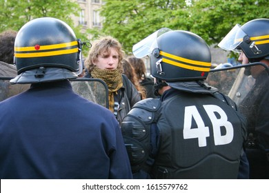 Paris, France - April 15 2008 - A man at a protest, framed by police officers wearing riot gear and holding shields at a protest of students and young people.  Image has copy space.
