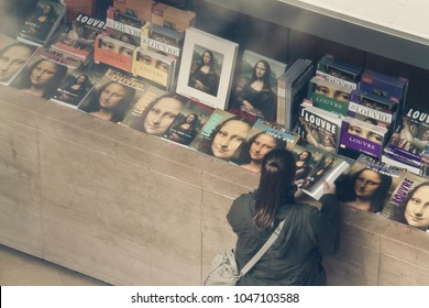 Paris / France  - April 15 2012: Tourist look at bookshelf of Monalisa face on  cover book in  Louvre museum