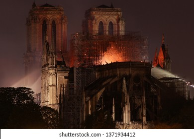 PARIS, FRANCE - APRIL 15, 2019: Burning roof of Notre Dame cathedral at night on April 15th 2019.